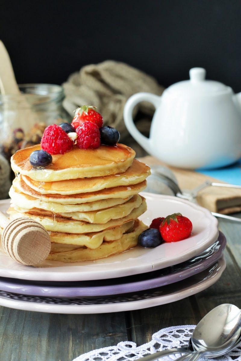 180 gr di farina 00 125 ml di latte fresco intero Zymil un vasetto di yogurt bianco Zymil 2 cucchiaini di lievito istantaneo vanigliato 2 uova 4 cucchiai di olio di semi di arachidi 2 cucchiai di sciroppo d'acero Per decorare: Frutta fresca e miele.